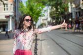 Young beautiful girl catches a taxi in big city — Stock Photo