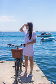 Pretty woman on bicycle in summmer vacation background the se — 图库照片