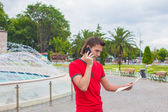 Young man using telephone with map in hands — 图库照片