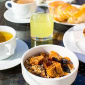 Leckeres Frühstück mit Flocken, Trockenfrüchten und Tasse Tee — Stockfoto