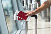 Closeup of man holding passports and boarding pass at airport — Stock Photo