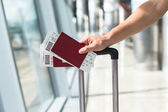 Close up of male hands holding passports and boarding pass at airport — Stock Photo