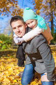 Family of two having fun in autumn park on sunny day — Stock Photo