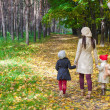 Little cute girls and young mother in autumn park — Stock Photo #51442059