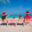 Happy family of four on beach in red Santa hats — Stock Photo