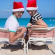 Family of two in Santa hats sitting on beach chair — Stock Photo #51442903