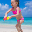 Happy little girl playing with toys at beach during vacation — Stock Photo #51443991