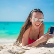 Young woman lying on white sand and talking by cell phone — Stock Photo #51444299