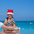Family of two in Santa hats sitting on beach chair — Stock Photo #51444683