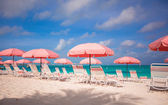 Cute umbrellas and sunbeds at tropical beach — Stock Photo