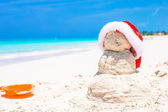 Sandy snowman with red Santa Hat on white Caribbean beach — Stock Photo