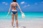 Back of young woman with sun cream and hat on beach — Stock Photo