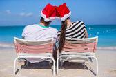 Young couple in Santa hats enjoy beach vacation — Stock Photo
