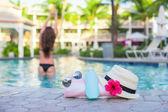 Woman, suncream, hat, sunglasses, flower and tower near swimming pool — Stock Photo