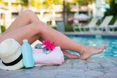 Sonnencreme, hut, sonnenbrille, blume und gebräunte weibliche beine pool — Stockfoto