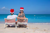Young couple in Santa hats during beach vacation — Stock Photo