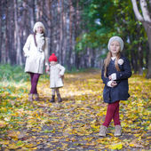 Little cute girls and young mother in autumn park have fun — Stock Photo