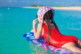 Little adorable girl on a surfboard in the turquoise sea — Stock Photo