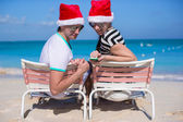Family of two in Santa hats sitting on beach chair — Stockfoto