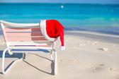Red Santa hat on beach chair — Stock Photo