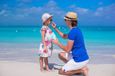 Father apply sunblock cream on his little daughter nose — Stock Photo