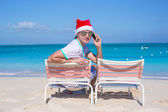 Back view of young man in Christmas hat at beach chair — Stock fotografie