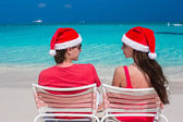 Happy romantic couple in red Santa Hats at tropical beach — Stock Photo