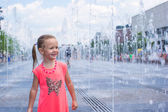 Little happy girl have fun in street fountain at hot sunny day — ストック写真