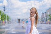 Little cute girl have fun in open street fountain at hot summer day — Stock Photo
