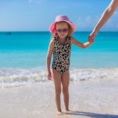 Cute little girl in shallow water at exotic beach — Stock Photo