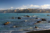 Rocky beach at Kaikoura, with snow capped mountains, South Island,New Zealand — Stock Photo