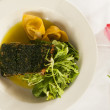 Salmon dinner on a white plate with a pink tulip. — Foto de Stock