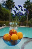 Vase with flowers and fruit by the pool — Stock Photo