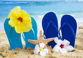 Flip flops and starfish with tropical flowers on sandy beach — Stock Photo