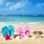 Flip flops and starfish with sunglasses on sandy beach — Stock Photo #27238073