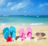 Flip flops and starfish with sunglasses on sandy beach — Stock Photo