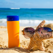 Sunscreen and starfish with sunglasses on sandy beach — Stock Photo
