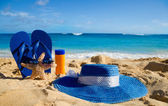 Flip flops, sunscreen, hat and starfish on sandy beach — Stock Photo