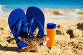 флип flops, солнцезащитный крем и морские звезды на песчаном пляже — Стоковое фото