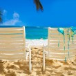 Beach chairs with flip flops by the ocean — Stock Photo #27409149