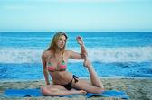 Yang kvinna utövar yoga av havet — Stockfoto