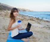 Yang woman with laptop by the ocean — Stock Photo