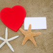 Heart shape, starfishes, and paper on the beach — Stock Photo