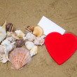 Two Heart shapes and paper on beach — Stock Photo #29211651