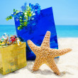 Stock Photo: Starfish with gifts on beach - holiday concept