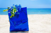 Gift bag on the beach - holiday concept — Stock Photo