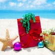Stock Photo: Starfish with gifts and christmas balls on beach