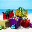 Gifts with Christmas ball on the beach — Stock Photo