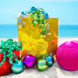 Stock Photo: Gifts with Christmas ball on beach