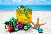 Starfish met giften en kerstballen op het strand — Stockfoto